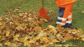Bottom of street worker piling up leaves stock video footage