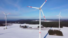Bottom up aerial view of a wind farm. Rotating wind power plants in a winter landscape
