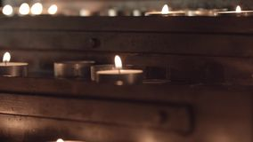 Church table for candles. Bottom-up panorama with focus changes from the candles at the bottom of the table to the candles at the top of the church table for stock footage
