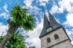 Church tower and tree against the blue sky. Bottom-up shot of Church bell tower and a tree in sunshine against a blue partially clowded sky royalty free stock images