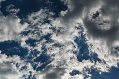 Bottom up view of greyish-white altocumulus clouds early in a summer morning. Beautiful dramatic cloud scape Royalty Free Stock Photography