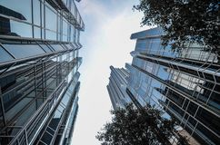 Bottom-up view of a tall Modern luxury Office Buildings in Canar Wharf, London. Bottom-up view of a tall Modern luxury Office Buildings with reflective glossy Stock Photos