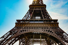 Bottom-up view to Eiffel tower. Paris, France. Blue vibrant sky with light clouds Royalty Free Stock Image