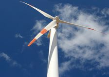 Bottom up view of a wind mill power generator. Wind mill power generator against a cloudy blue sky Stock Image