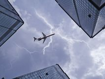 Bottom view of airplane flying above skyscraper Stock Photo