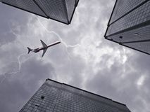 Bottom view of airplane flying above skyscraper Royalty Free Stock Image