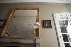 Bottom view of the antique mirror above the mantelpiece and the facet mirror in an old apartment on Place Vendome in Paris. Paris, France - July 05, 2018: Bottom royalty free stock image