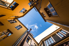 Bottom view from the atrium of the red houses in Riga. Bright orange home form at the top of the atrium which shows blue sky. Photographed at the wide angle from Royalty Free Stock Photo