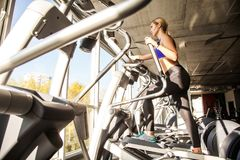 Bottom view of blonde woman in fitness club, ride on orbitrack royalty free stock photo