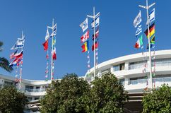 Bottom view on the bright, fluttering flags of various countries against the blue sky and the hotel, Eilat, Israel. EILAT, ISRAEL – November 7, 2017: Bottom Stock Photo