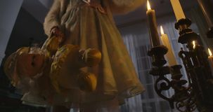 Bottom view of Caucasian girl in dress standing next to the candlestick with candles and holding doll. Weird child alone
