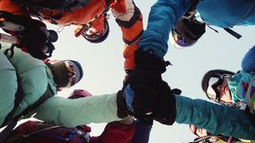 Bottom view of the company of climbers, which stands in a circle, puts his hands together, shakes them and raises up. Bottom view of the company of climbers stock video