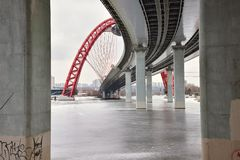 Bottom view between concrete pillars on the road bridge with a red arch. The Picturesque bridge over the Moscow River, Picturesque bridge with a flying saucer royalty free stock photo