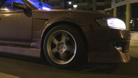Bottom view of cool car driving on night city. Action. Shiny dark gold finish with glitter on car driving through night. City and sparkling from light of stock footage