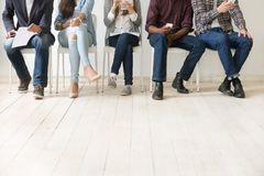 Bottom view of diverse work candidates waiting for job interview. Close up view of diverse work applicants sitting together, holding smartphones, tablets and royalty free stock images