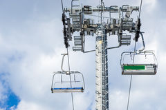 Bottom view on empty ski lift with seats in a ski-resort. Bottom view on empty ski lift with seats against cloudy sky in a ski-resort Royalty Free Stock Photography