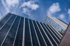 Bottom view of facades of modern glass office buildings and blue sky up it. Bottom view of facades of modern glass office buildings and beautiful summer blue Royalty Free Stock Photo