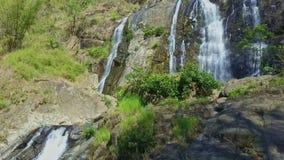 Bottom view fantastic waterfall among tropical woods. Bottom view fantastic large high waterfall on cliff rocks among wild tropical woods on mountain stock video