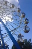 Bottom view of a ferris wheel with yellow closed cabins on a background of blue sky with clouds on a summer sunny day stock photography
