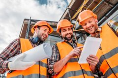 bottom view of group of builders with blueprint and tablet stock image