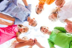 Bottom view of group of happy schoolchildren standing in circle stock photography