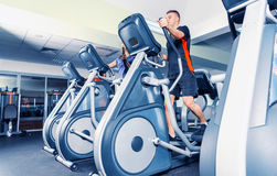 Bottom view on group of young people diligently exercising on th. E crosstrainer machines in fitness center Stock Images