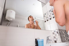 Bottom view of handsome man shaving in the bathroom. Bottom view of handsome man shaving his face standing in front of mirror with washbasin in the modern tiled Royalty Free Stock Images