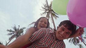 Bottom view of happy girl on the shoulders of her man holds balloons having fun on palm trees on the background. A. A loving couple enjoying vacation on a stock footage