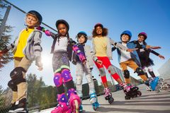 Happy kids rollerblading with hands like wings Stock Photography