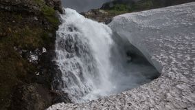 Bottom view of high waterfall falling in snowfield. Kamchatka Peninsula mountain landscape - bottom view of high waterfall falling in snowfield on cloudy day stock footage