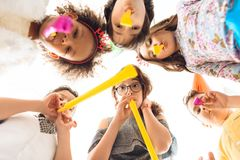 Bottom view. Joyful children are blowing on festive pipes at birthday party. Children`s fun concept. Kids are celebrating birthday party stock image