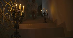 Bottom view of ladder with two candlesticks. Little Caucasian girl in beautiful dress coming out from the room upstairs