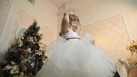 Bottom view of a little girl in holiday dress with lush magic twig in his hands. Bottom view of a little girl dancing in a festive dress with lush magic twig in stock video footage