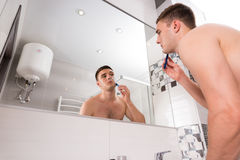 Bottom view of male shaving his face in the bathroom. Bottom view of male shaving his face standing in front of mirror in  the modern tiled bathroom at home Stock Photo
