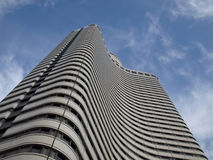 Bottom view on modern high rise building. In wavy design over blue sky Stock Photography