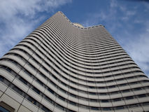 Bottom view on modern high rise building. In wavy design over blue sky Royalty Free Stock Images
