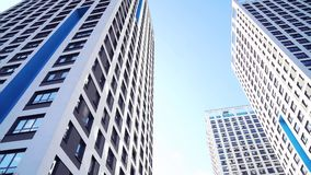 Bottom view of new residential high-rise buildings with blue sky. Urban environment. Frame. Newest residential complexes stock footage
