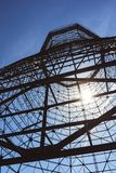 Bottom view of old cooling tower. In front of blue sky with sun stock photos