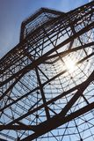 Bottom view of old cooling tower. In front of blue sky with sun stock images