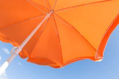 Bottom view of orange parasol against a blue sky Royalty Free Stock Image