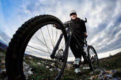 Bottom view photo of cyclist in the black sportwear standing with his bike on the rock against blue sky with clouds. Stock Images