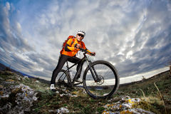 Bottom view photo of cyclist in orange jacket standing with his bike on the rock against blue sky with clouds. Stock Photography