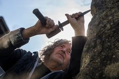 Bottom view of sculptor sculpting with chisel and hammer. In stone under blue sky stock images