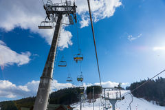 Bottom view on ski lift with seats going over the mountain. And paths for skies and snowboards in a ski-resort Stock Photography