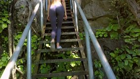 Bottom View Slim Girl Goes up Wooden Stairs in Park. Bottom view slim long legged girl goes up old wooden stairs with railings among tropical plants against stock video footage