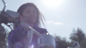 Bottom view of the smiling happy girl sitting on the motorcycle talking by cellphone close-up. Sun shining into camera. Bottom view of the smiling happy girl stock footage