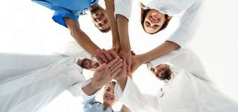 Bottom view.a team of doctors at the medical center clasped their hands together royalty free stock images