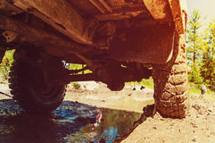 Bottom view to big offroad car wheel on country road. And forest backdrop. off-road the car passes the obstacle off-road in the mud. race rally stock image