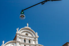Bottom view of Traditional street lamp and an famous old Venetian church building in the middle of the day with a blue Stock Image
