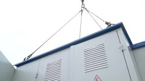 Bottom view of a transformer box that rotates in the air suspended on a construction crane stock footage